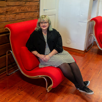 Tiina Heikka sitter i en designfåtölj.
