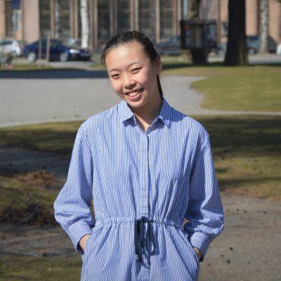 En leende kvinna står i en park.