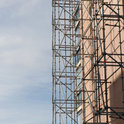 Vasemmalla kuvassa on taivasta ja oikealla kuvassa on rakennustelineitä pystytettynä talon seinään.