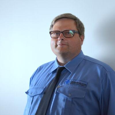 ledande nödcentralsoperatör ralf björklund i blå skjorta med vit vägg i bakgrunden.