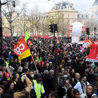 Hav av människor i Paris under jättedemonstration mot pensionsreform. Flera håller upp banderoller och flaggor.