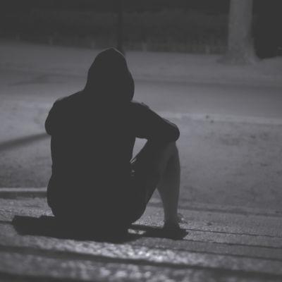 Kille med huva sitter på en utomhusstentrappa med ryggen mot kameran. Svartvit bild.