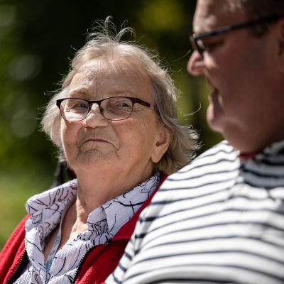 Markku Kostiainen istuu puistonpenkillä iäkkään äitinsä Raili Kostiaisen kanssa.