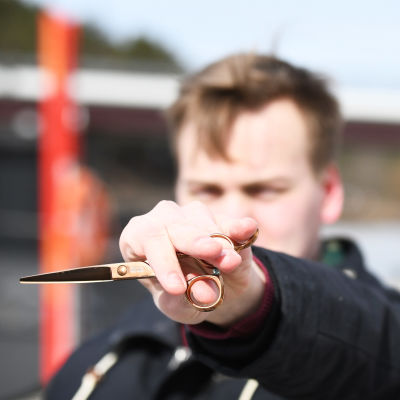 Axel Nylund håller upp en sax.