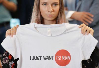 """Kristina Tsimanovskaja under en presskonferens i Warszawa. Hon håller upp en t-skjorta med texten """"I just want to run""""."""