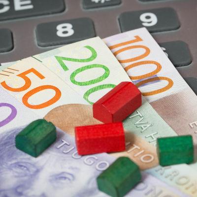 Röda och gröna miniatyrhus ovanpå svenska sedlar.