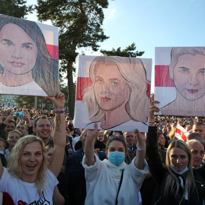 Kvinnor håller upp plakat med bilder på centrala oppositionsfigurer under en demonstration i Minsk.