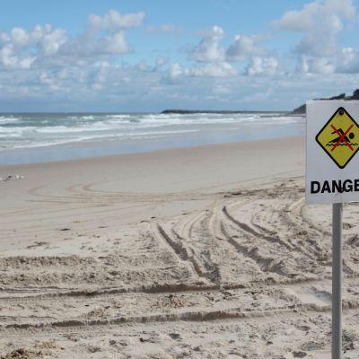 Hiekkarannalla kyltti jossa uimarin kuvan päälle vedetty punainen ruksi sekä teksti vaara