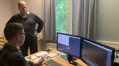 En man står intill ett bord där en kvinna sitter och jobbar vid en dator.