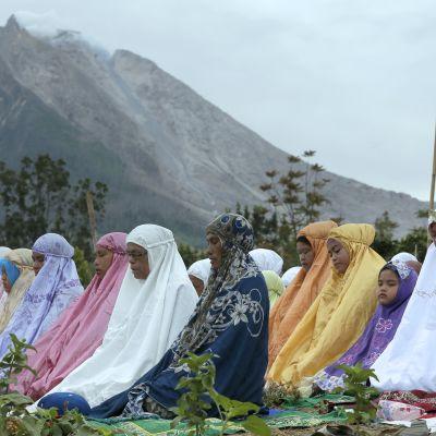 Naisia istuu maassa rukoilemassa. Taustalla vuori.