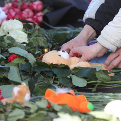 Blommor och nallebjörn som sörjande lägger ner efter branden i Kemerovo