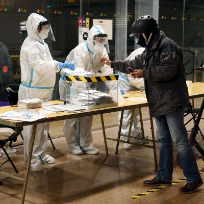 En person röstar i Barcelona vid en tidpunkt som reserverats för covid-19-smittade.