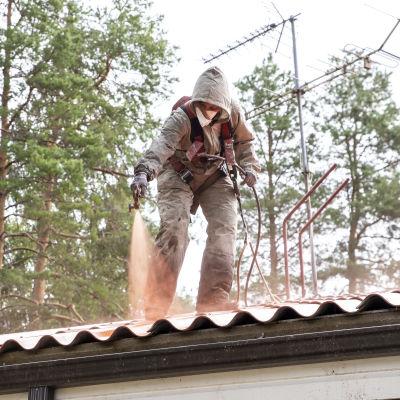 Maalari maalaa ruiskulla omakotitalon kattoa.