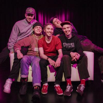 Viisihenkinen räp-yhtye Aarnikotkat sohvalla. Henkilöt vasemmalta oikealle: MC Pösö, Carlito, Santana, Rumilus ja Leo G