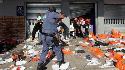 En polis siktar på människor som är i färd med att plundra ett köpcenter i Durban under politiska våldsamheter.