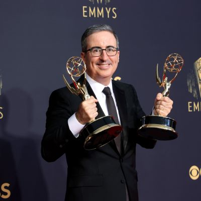 John Oliver poserar med två Emmystatyetter.