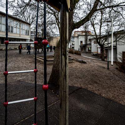 Molnig och regnig dag på en lågstadieskolgård. En grupp barn går mot vit matsalsbyggnad.