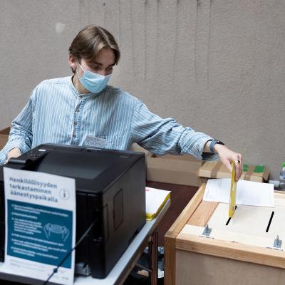 Vaalityöntekijä tiputtaa äänen vaaliuurnaan.
