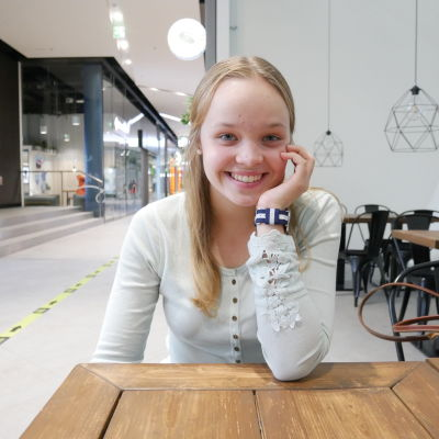 Julia Huovinen sitter vid ett bord, ler och lutar huvudet i handen.