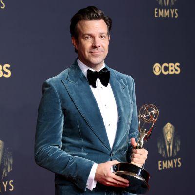 Jason Sudeikis poserar med sin Emmystatyett. Han är klädd i en blå sammetskavaj och svart fluga.