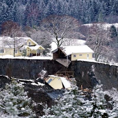 Bild på jordraset. Ett gult hus står oskadat nära kanten. Alldeles invid kanten finns ett hus som dels rasat in i gropen. Dess ena yttervägg syns i gropen.