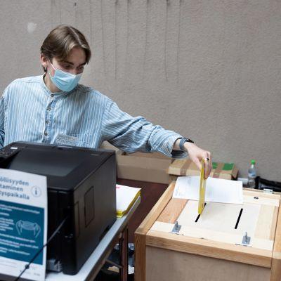 En valarbeterare lägger in en röst i valurnan.