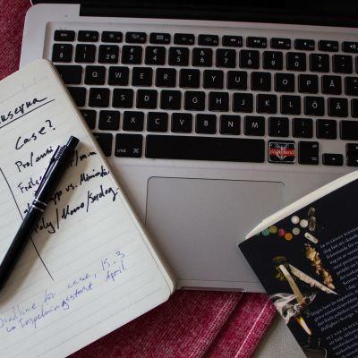 Ett skrivbord med en bok om knark, en dator och ett anteckningsblock.