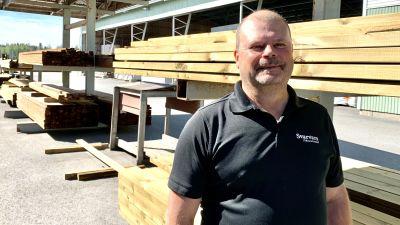 En man i kortärmad skjorta står intill en hög med bräder.