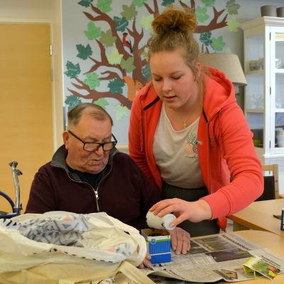 En äldre man och elev sitter vid ett bord och häller mylla i en ask.
