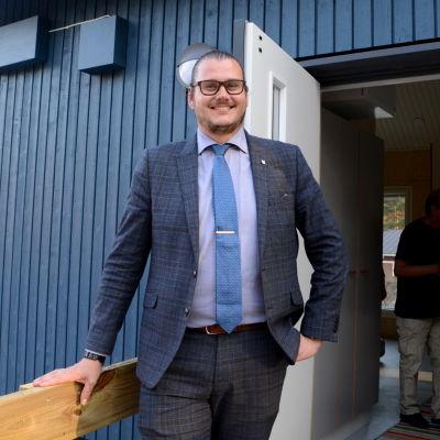 En man står i dörröppningen till ett blått trähus.