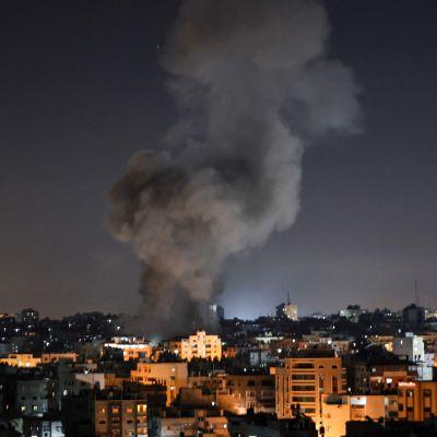 Rök stiger över byggnader i Gaza efter bombningar tidigt under lördagsmorgonen 15.5.2021.