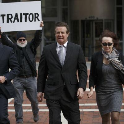 MAnafort på väg in i rättegång med frun och demonstrant i bakgrunden