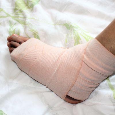 En stukad fot på en säng.