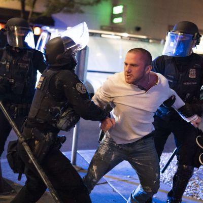 Två poliser håller i en man med vit skjorta som ser ut att kämpa emot.