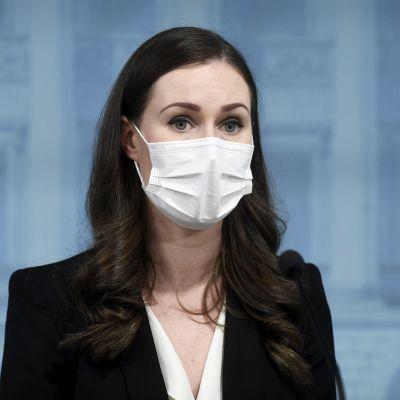 Statsminister Sanna MArin i närbild med munskydd på sig.
