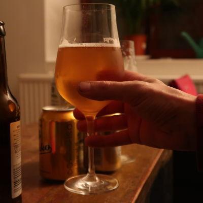 En hand lyfter ett vinglas med öl.