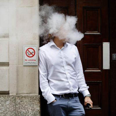 En man står framför en vägg och röker en e-cigarett. Huvudet är täckt i ett rökmoln.