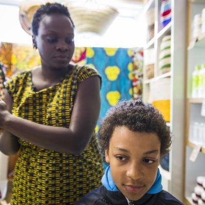 Harriet Aryenda  laittaa Sandoo Mäenpään hiuksia