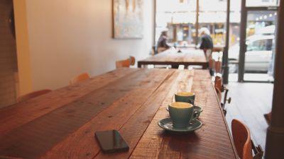smarttelefon och två tomma koppar på bord i kafé
