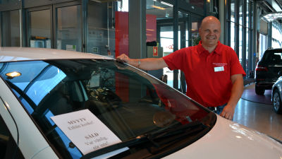 Bilförsäljare Jens Wistbacka i Vasa intill en såld bil.
