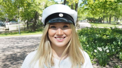 Linnea Aula som tar studenten i år 2020 med studentmössa på sig. Hon är fotad ute i försommargörnskan.