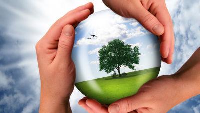 Tre händer håller om en glob med ett träd, mark och atmostfär.