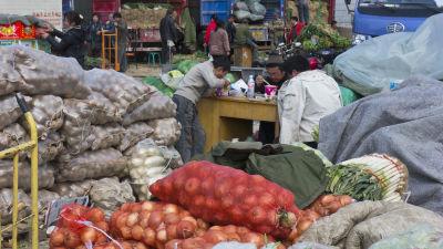 Tre män äter lunch omringade av enorma påsar med råvaror såsom lök och purjo.