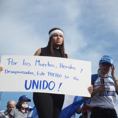 En ung kvinna med pannband håller upp en skylt med texten Por los Muertos, Heridos y Desaparceidos, este Pueblo se ha Unido!