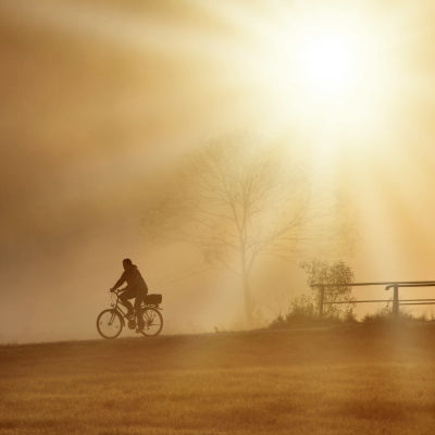 Cyklist i dimman över ett öppet landskap.