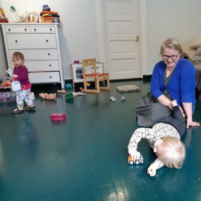Hanna Räisänen sitter på golvet med två barn som leker med leksaker.