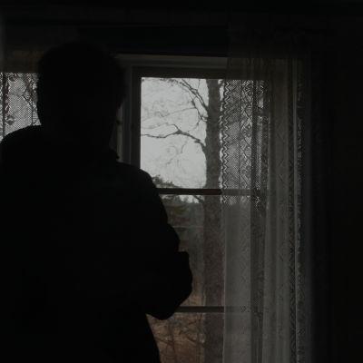 En anonym person står vid ett fönster. Utanför syns bara träd.