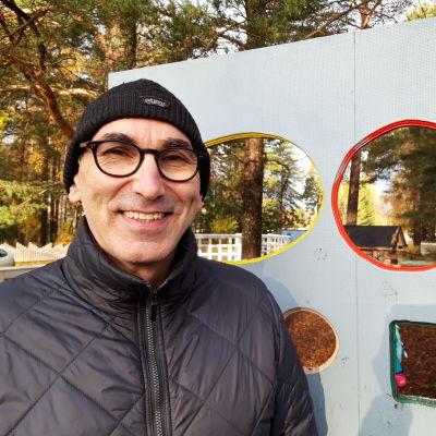 Kasvatustieteilijä, filosofi Juha Hakala seisoo lasten leikkitelineen edessä syksyisessä maastossa.
