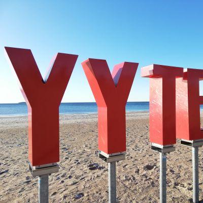 Hiekassa punaiset muovikirjaimet, jotka muodostavat sanan Yyteri.