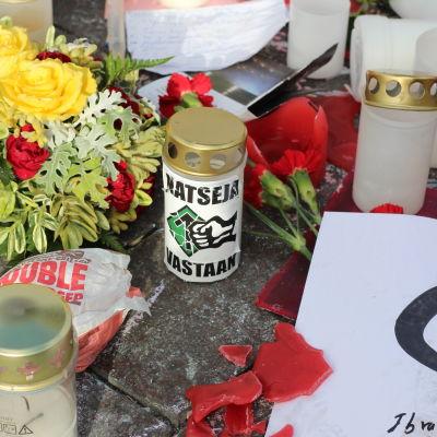 Blommor och ljus vid den plats där en person misshandlades till döds i Helsingfors.